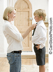 Woman in front hallway fixing young boy\\\'s tie and smiling