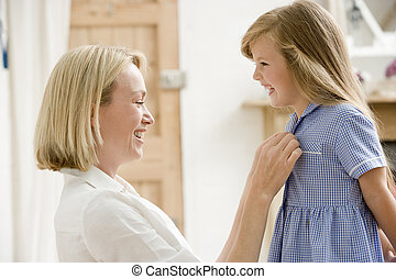 Woman in front hallway fixing young girl's dress and smiling