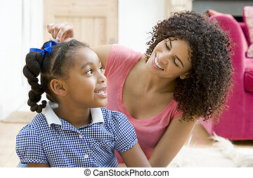 Woman in front hallway fixing young girl's hair and smiling