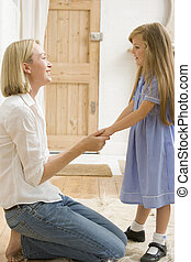 Woman in front hallway holding young girl's hands and smiling