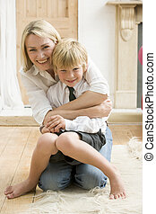 Woman in front hallway hugging young boy and smiling