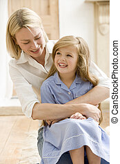 Woman in front hallway hugging young girl and smiling