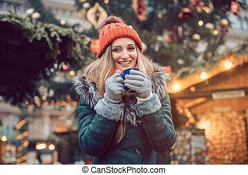 Woman in front of Christmas tree on winter market drinking hot wine