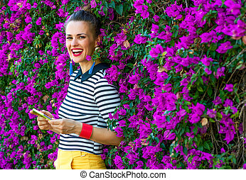 woman in front of colorful magenta flowers bed writing sms -...