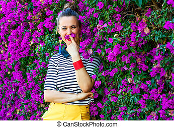 woman in front of colorful magenta flowers bed having fun...