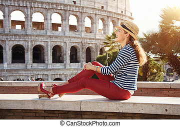 woman in front of Colosseum looking into distance while sitting