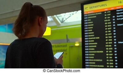 Woman in front of flight information board, checking her ...