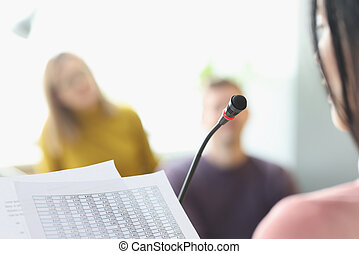 Woman in front of microphone reading information from paper closeup