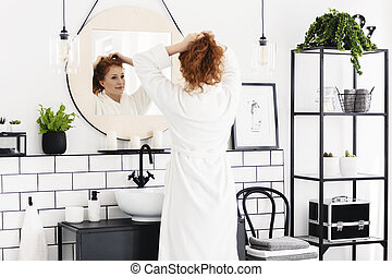 Woman in front of mirror in minimal bathroom interior with poster, chair and plants. Real photo