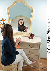 Woman in front of mirror - Young girl is sitting in front of...