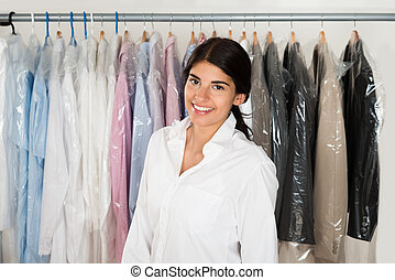 Woman In Front Of Rack With Hangers - Young Happy Woman...