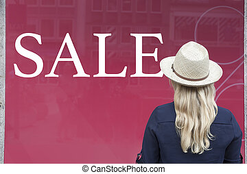Woman in front of shop window with