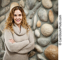 Woman in front of stone wall