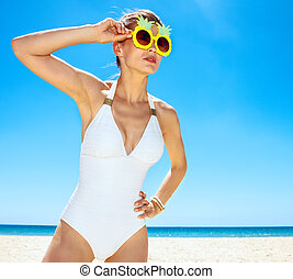 Woman in funky pineapple glasses looking into distance at beach