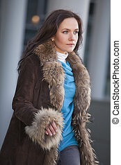 woman in fur coat walking on the street