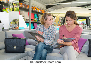 woman in furniture store with shop assistant discussing colors