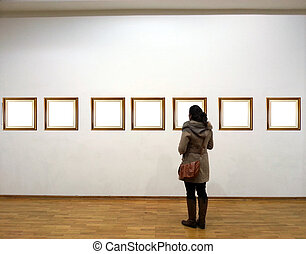 Woman in gallery room looking at empty frames