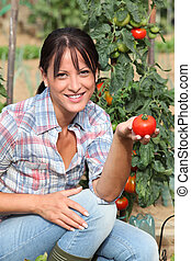 Woman in garden kneeling by tomato plant