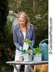 Woman in garden ready to water fresh plants