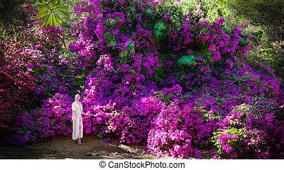 Woman in garden with purple flowers.