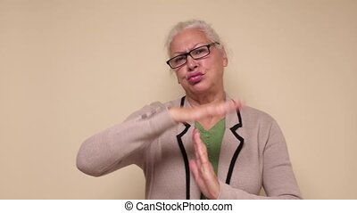 Senior caucasian woman in glasses in glasses doing time out gesture with hands, frustrated and serious face