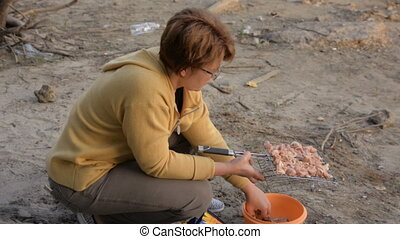 Woman in glasses lays meat on the grill for a barbecue....