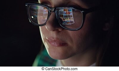 Woman in glasses looking on the monitor and surfing...
