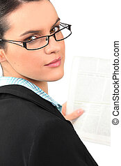 Woman in glasses reading a document