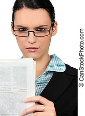 Woman in glasses reading a newspaper