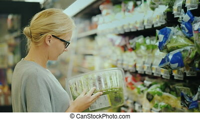 Woman in glasses selects products in the supermarket fresh...