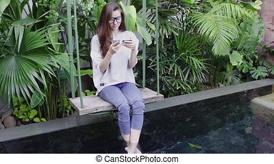 Woman in glasses shopping online with smartphone and credit card while sitting on swing near pool in tropical country.