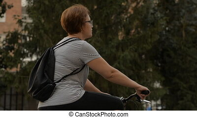 Woman in glasses starts on a bicycle in the park