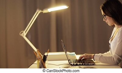 woman in glasses typing on laptop at night office -...