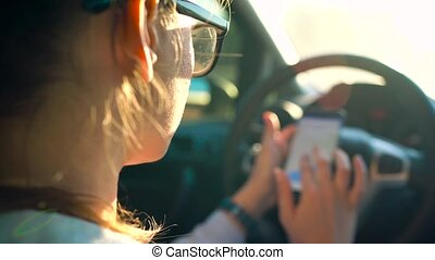Woman in glasses using a smartphone in the car