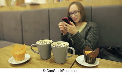 Woman in glasses using app on smartphone in cafe drinking coconut coffee smiling and texting on mobile phone. Beautiful young casual female talking with her friend and uses mobile phone.