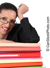 Woman in glasses with a stack of files