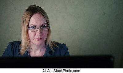 woman in glasses works behind a computer