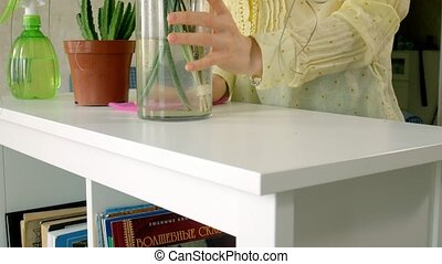 Woman in gloves cleaning furniture with rag at home living room.