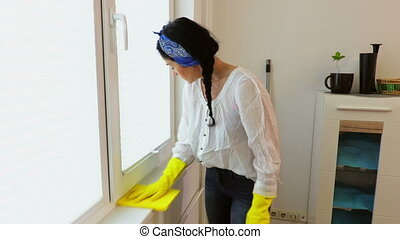 Woman in gloves cleaning window furniture with rag