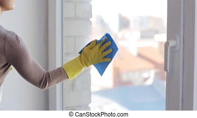 woman in gloves cleaning window with rag - people, housework...