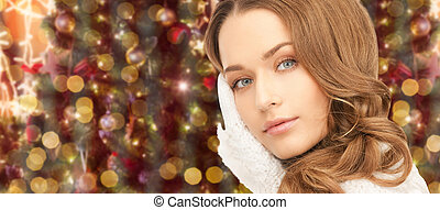 woman in gloves over christmas lights background