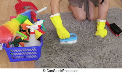 Woman in gloves with brush on faux fur rug. Housekeeping and cleaning concept