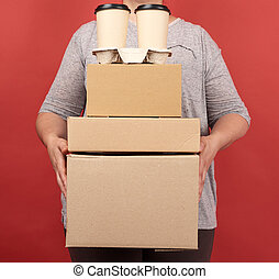 woman in gray clothes holds a stack of brown paper boxes and disposable glasses with coffee on a red background