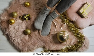 Woman in warm gray socks sits on a fur skin around boxes with gifts and gold colored Christmas decorations. The concept of a cozy happy holiday at home. Merry christmas and new year. Close up. Slow motion.