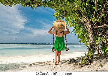 Woman in green dress swinging at beach - Woman in green...