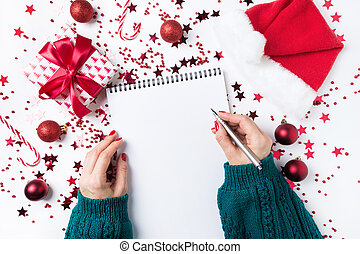 Woman in green sweater writting checklist of plans and dreams for next year. Wish list for Christmas. To Do List for New 2020 year with red Holiday decor.