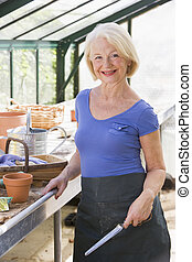 Woman in greenhouse holding shovel and smiling