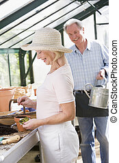 Woman in greenhouse planting seeds and man holding watering can smiling