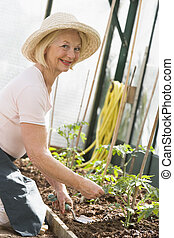 Woman in greenhouse planting seeds smiling