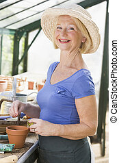 Woman in greenhouse putting seeds in pot and smiling